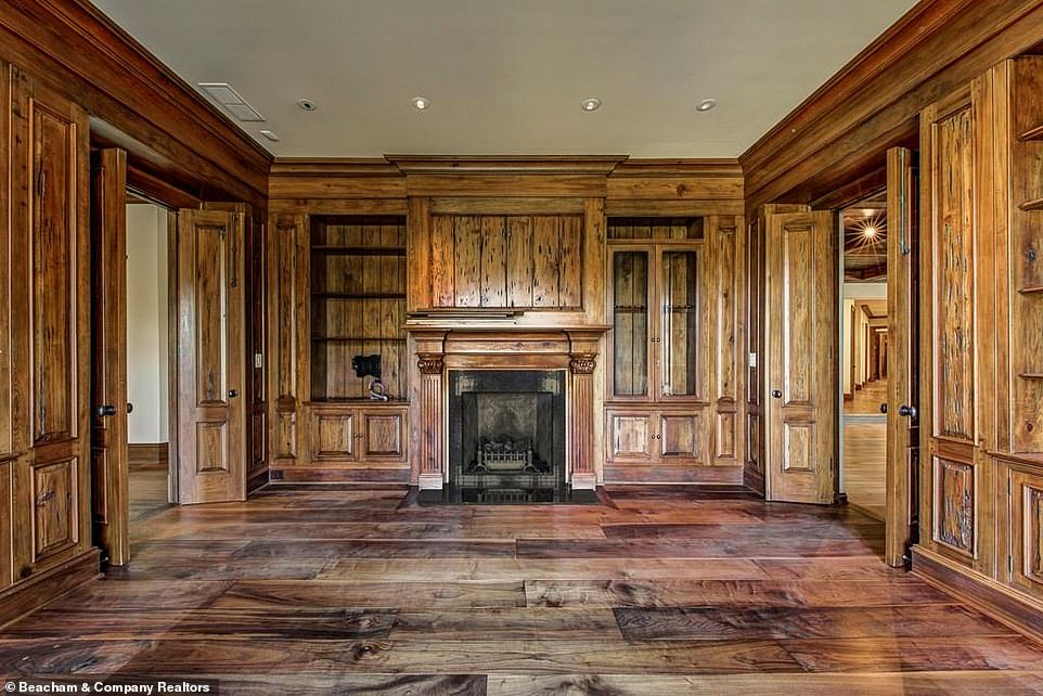 Lovely:The library similarly evokes an old-fashioned feel, with the walls and shelving done entirely in exposed wood and a fireplace set in between the two doors