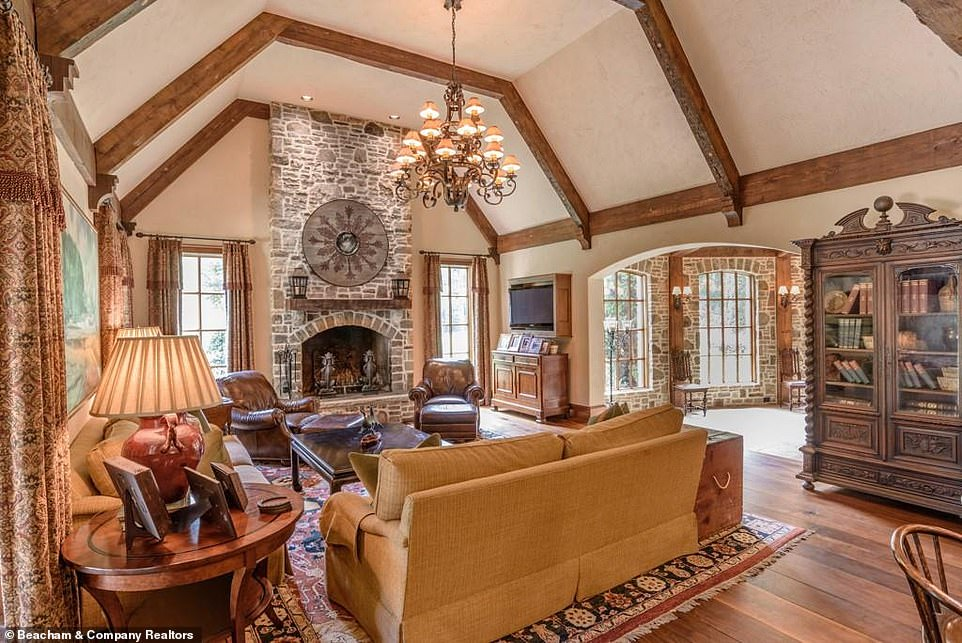 A perfect place for teatime:Another sitting room is arranged around a large stone fireplace and boasts not only an extravagant chandelier but also a massive bookcase as a homey touch