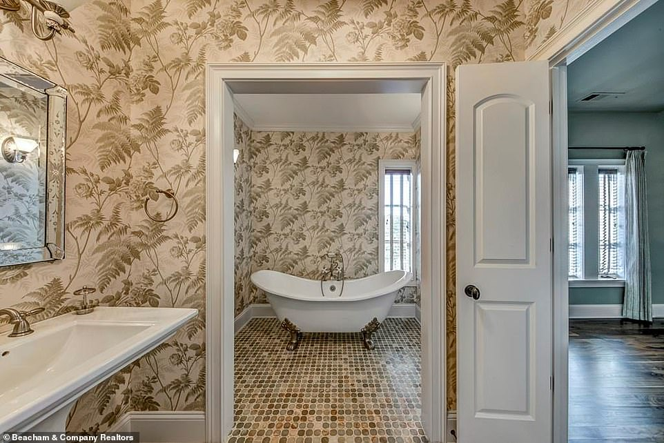 Coordinated:The ensuite's wallpaper has a pale leafy green motif to match the bedroom, as well as green, browna nd white tiling in the room that contains the large ceramic tub