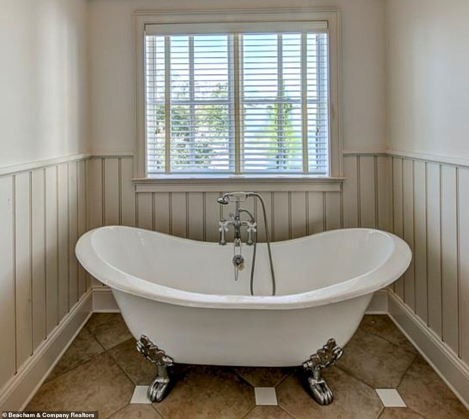 Perfect place to relax:A similar tub - old-fashioned and detached with metallic legs designed to look like actual feet - sits in another narrow bathroom this time reminiscent of the colonial era
