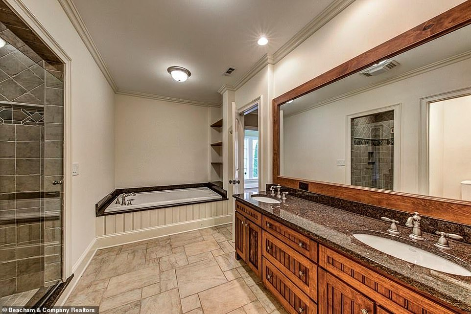 Luxe to the hilt: A smaller bathroom is still handsomely appointed with log-cabin-chic wood paneling around the mirror to match the cabinets underneath the sinks
