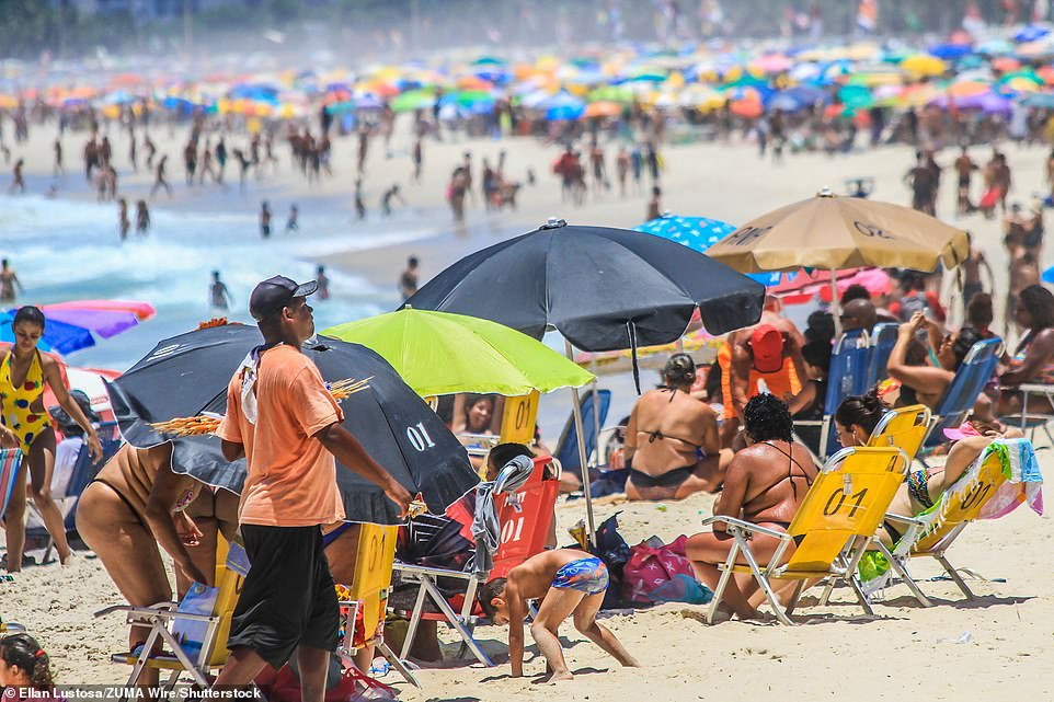 Thickets of umbrellas and sunbathers cover the golden sands of the beach on Friday