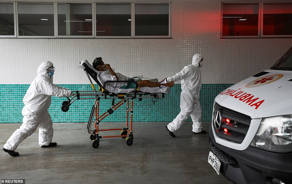 Emergency: Healthcare workers transport a 77-year-old patient on a stretcher at a Manaus hospital after he came down with coronavirus symptoms, as a new strain which is feared to be more contagious spreads across the Amazon