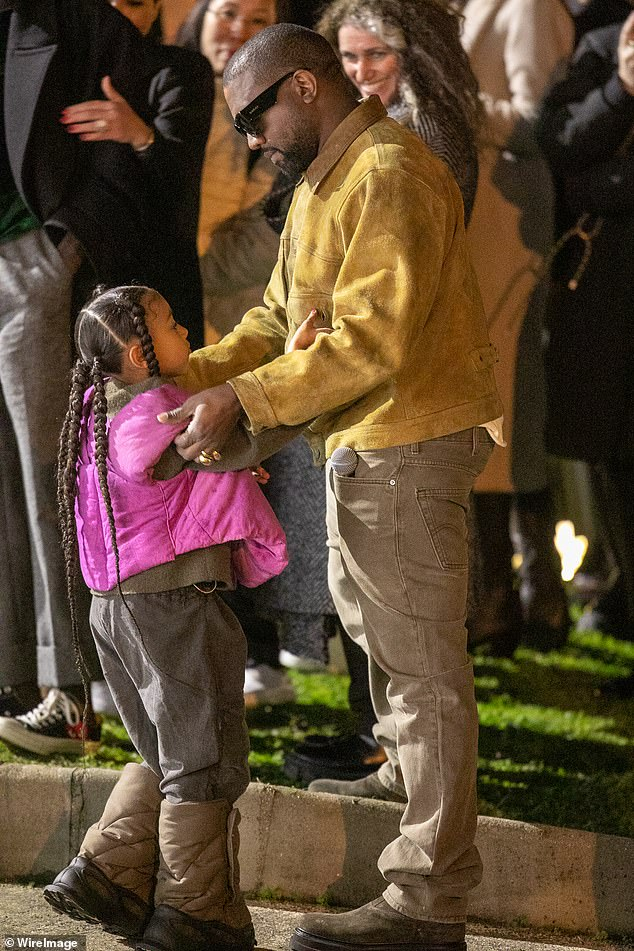 Proud founder: West describes his foot line as 'the Lamborghini of shoes', a nod to the matte-black Lamborghini SUV he owns; West seen with his eldest daughter North at the Yeezy Season 8 last year
