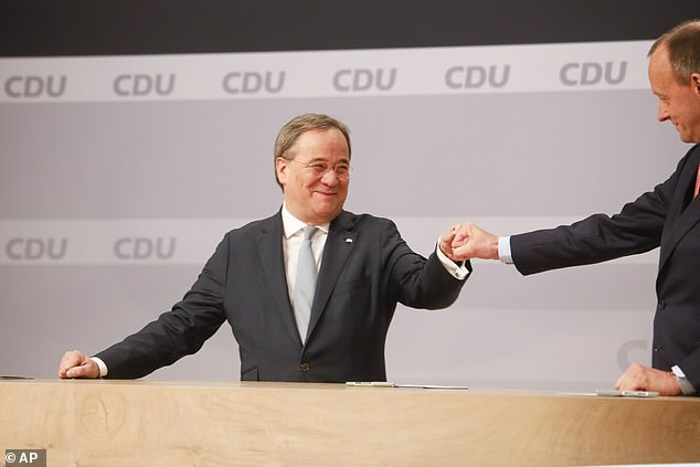 Laschet, left, fist bumps his rival candidate Friedrich Merz during the final vote count today