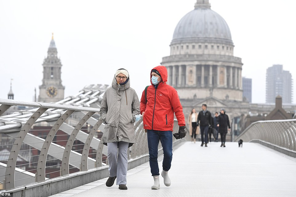 People walk in the rain over Millennium Bridge in London. Parts of eastern England saw up to three inches of snow