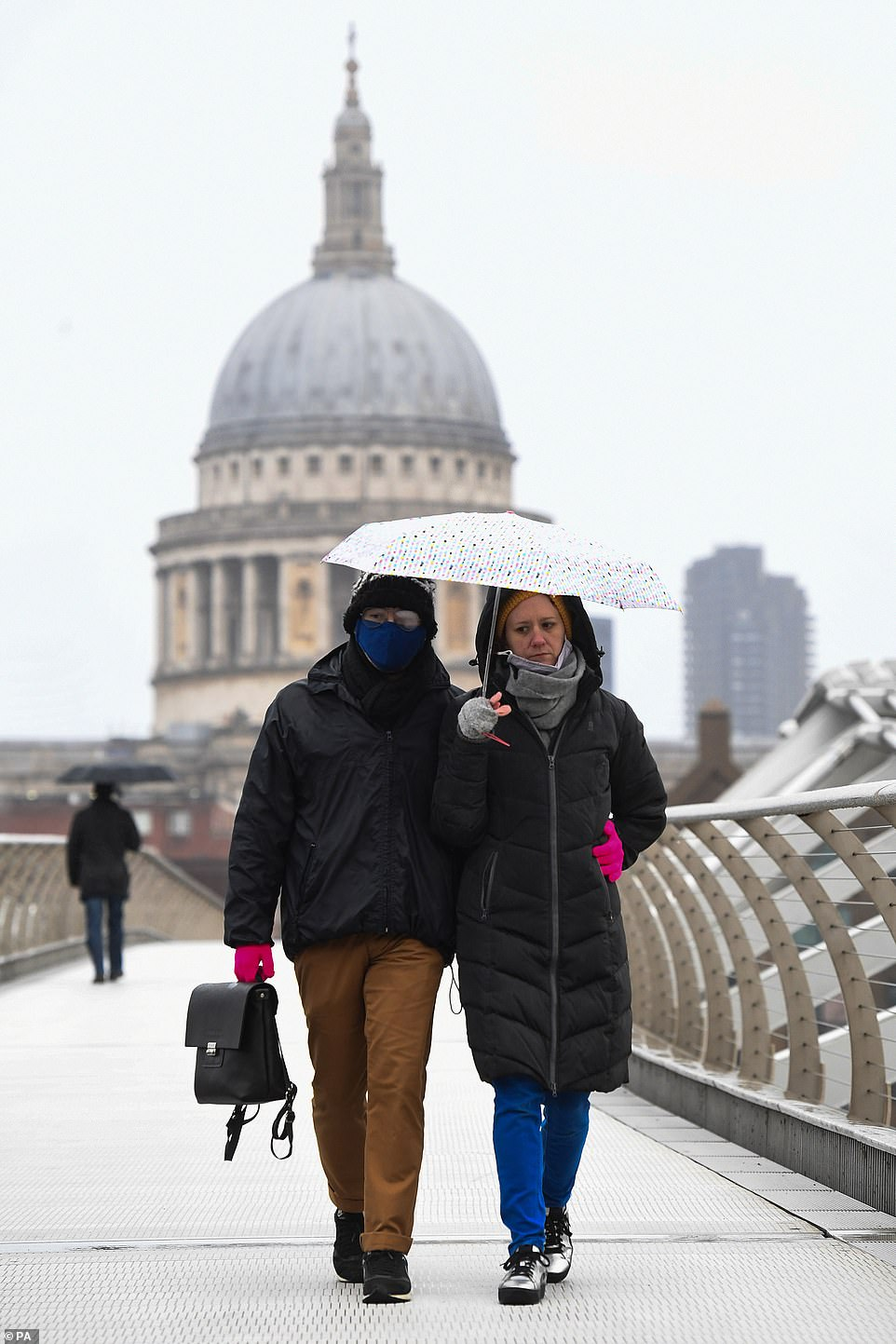 People walk in the rain over Millennium Bridge in London as heavy rain struck the capital on Saturday afternoon