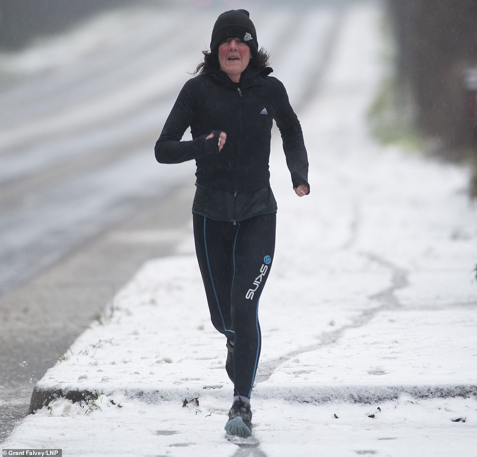 An early morning runner in the snow in Sevenoaks, Kent, looks flushed as she exercises in freezing conditions