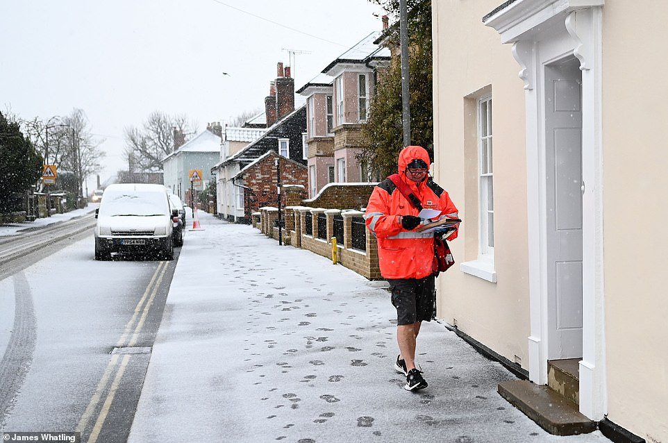 A postman braves the snow in his shorts as he made his deliveries in Maldon, Essex, this morning