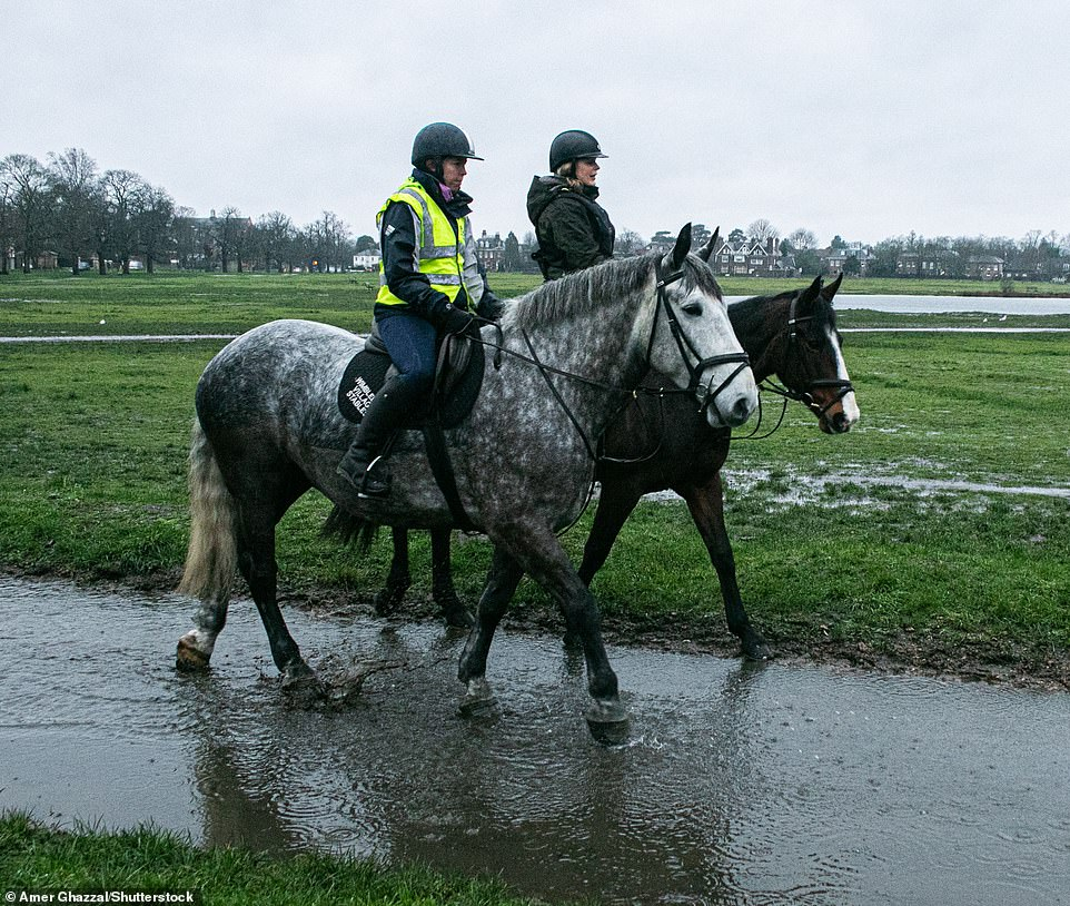 Horse riders head through a waterlogged Wimbledon Common on a cold morning due to heavy rain this morning