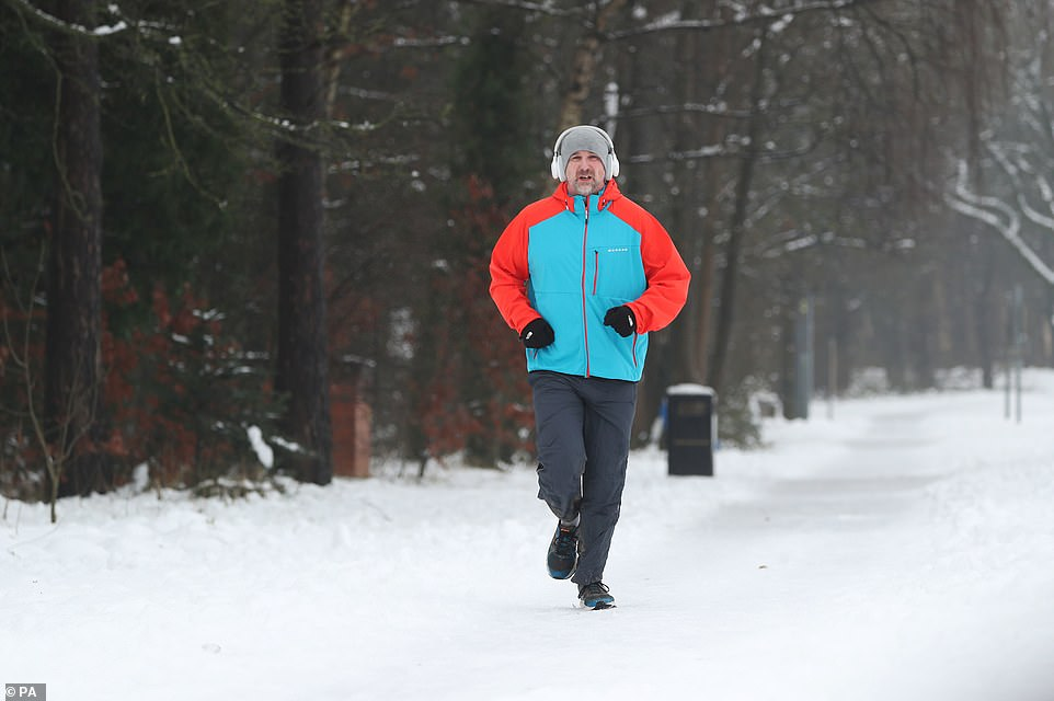 A man jogs down a snow covered street in Catterick, North Yorkshire, as the north of England woke up to a blanket of snow