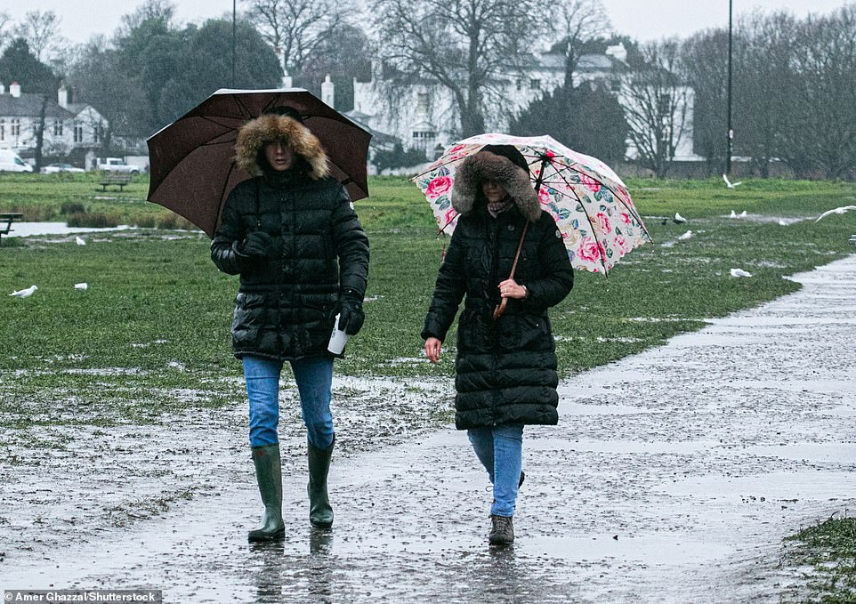 Walkers shelter underneath the hoods of their coats and umbrellas as they head through heavy rain on Wimbledon Common