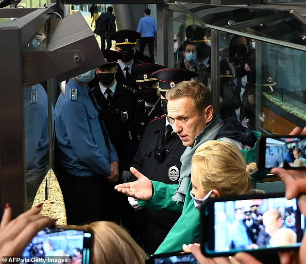 Kremlin critic Alexei Navalny (green coat) was arrested by Russian authorities just minutes after landing in Moscow with wife Yulia (front of frame in mask)