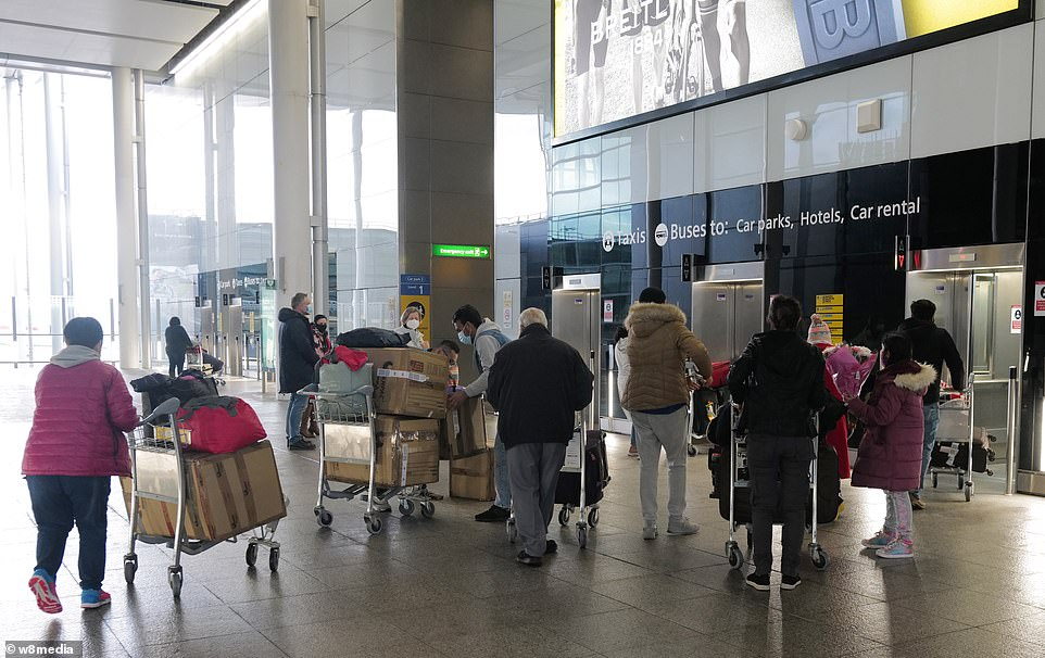 Air passengers push their luggage trolleys through the arrivals hall at London Heathrow Airport's Terminal Two this morning