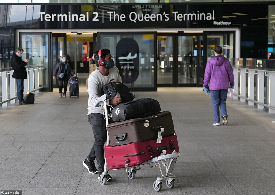 An air passenger walks out of Heathrow Airport's Terminal Two this morning as people continue to arrive in Britain