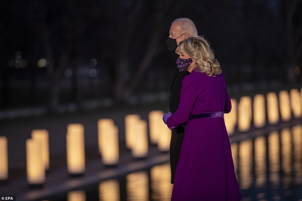 Joe and Jill Biden huddle together to mourn the lost lives of more than 400,000 Americans on Tuesday night in DC