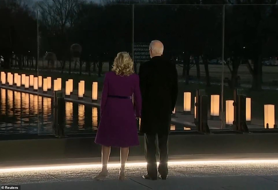 The Bidens hold hangs as they stare out over the Reflecting Pool during the memorial on Tuesday