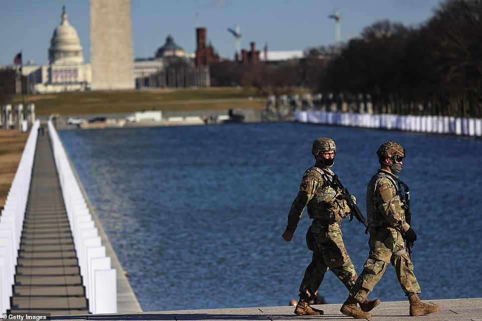 National Guard soldiers patrol the grounds of the Lincoln Memorial ahead of the COVID memorial on Tuesday afternoon