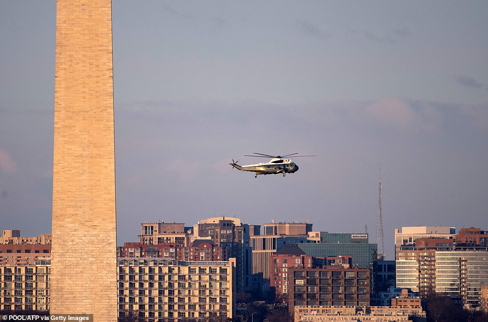 Marine One flies by the Washington Monument on its way to the White House in Washington, DC, on January 20, 2021, for the departure of US President Donald Trump