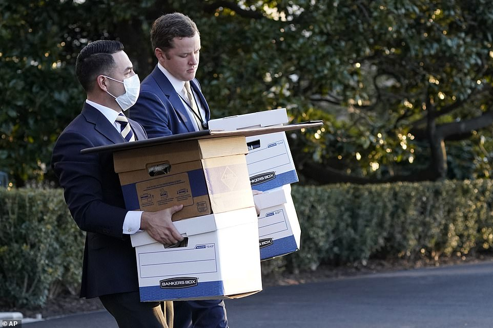 White House staff members carry boxes to Marine One before President Donald Trump leaves the White House, Wednesday, Jan. 20, 2021