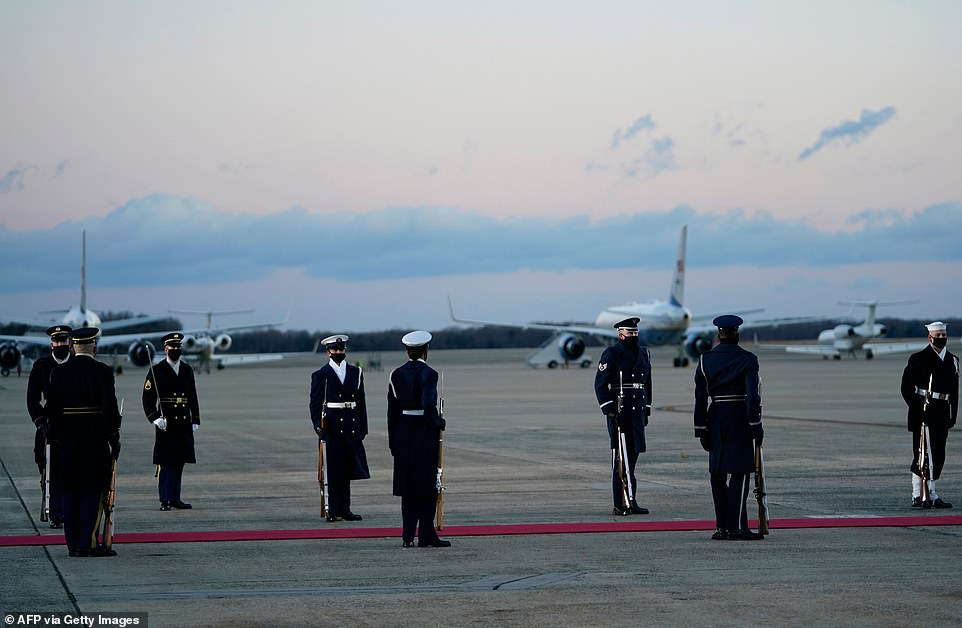 Honor guard ready: A military escort including soldiers and sailors waits beside the red carpet at Joint Base Andrews