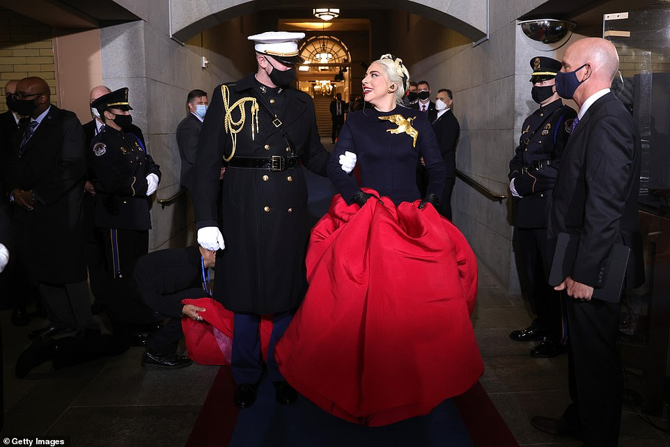 Gaga sported a black top and billowing red skirt, with a gold bird pinned on her top, as she was accompanied down the steps to sing the Star-Spangled Banner