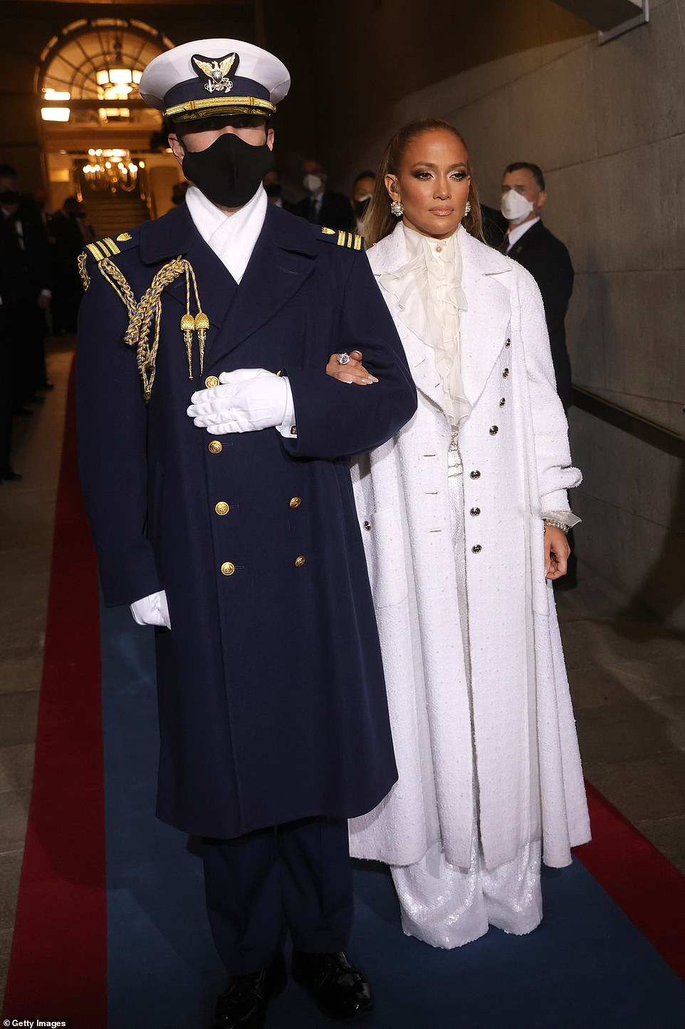 Jennifer Lopez is escorted to the stage for her performance. She was dressed head-to-toe in white Chanel