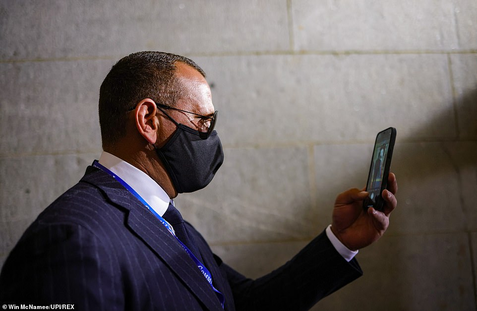 Former New York Yankee Alex Rodriguez takes a photograph with his phone