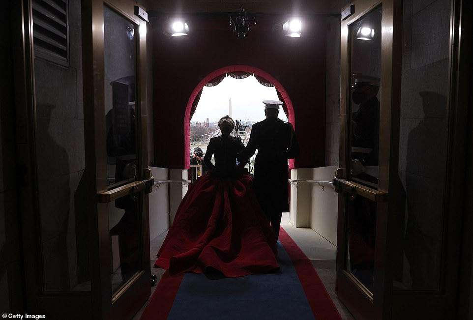 Lady Gaga is escorted to the stage to perform the national anthem in her spectacular inauguration day outfit