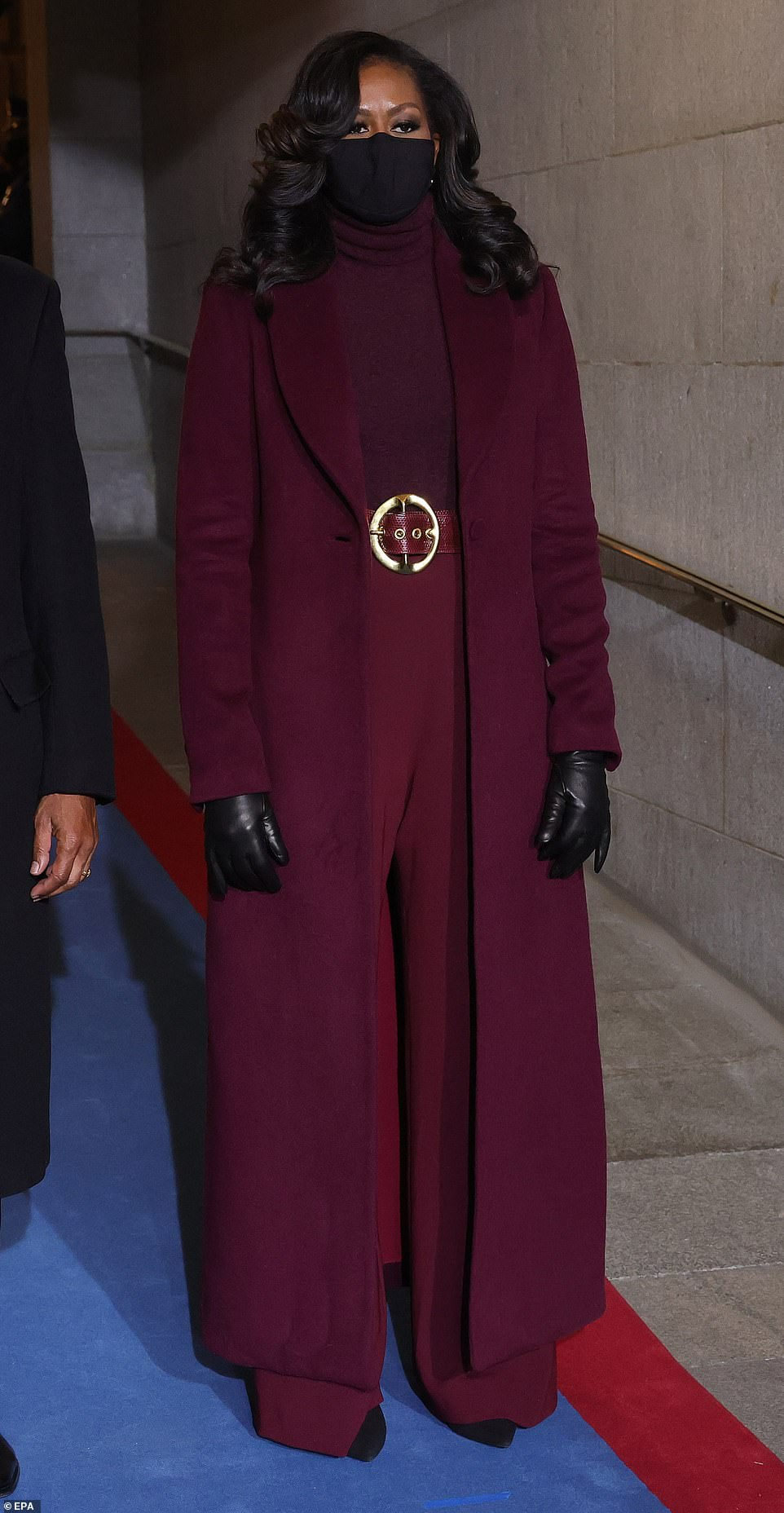 Monochrome: Mrs. Obama wore a floor-length coat over a form-fitting turtleneck and wide-leg pants by Sergio Hudson