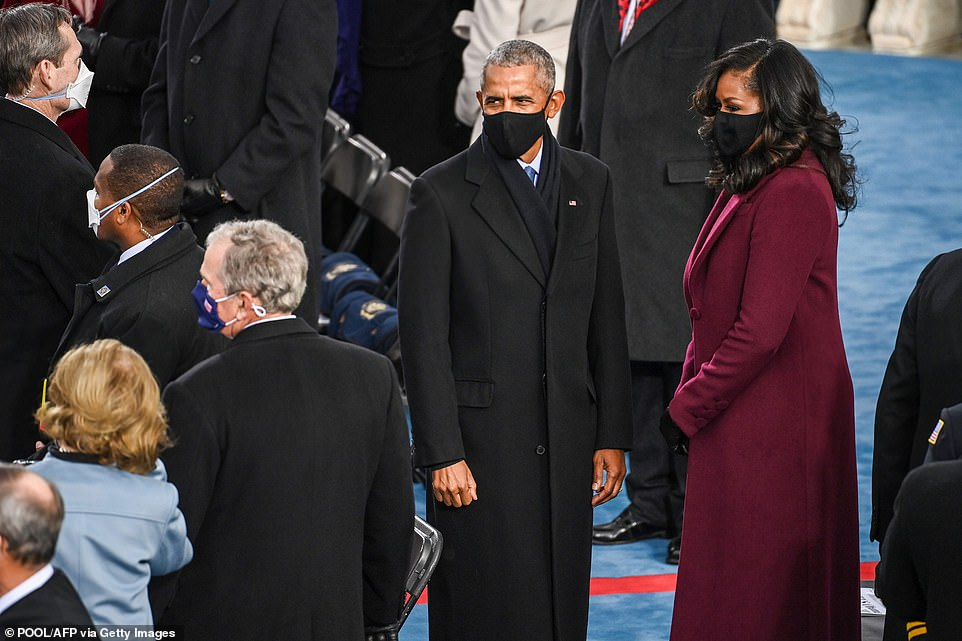 Looks: The Obamas matched in their full-length coats, though the former President opted for classic black