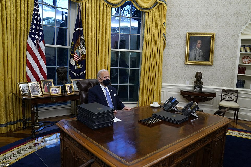 Biden wore a face mask as he sat behind the Resolute Desk to sign the executive orders. The visual was a stark change to former President Trump, who rarely wore a covering. 'I thought there's no time to wait,' he said. 'There's no time to start like today'