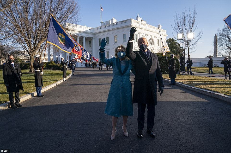 President Joe Biden and first lady Jill Biden pause to wave while walking toward the North Portico of the White House