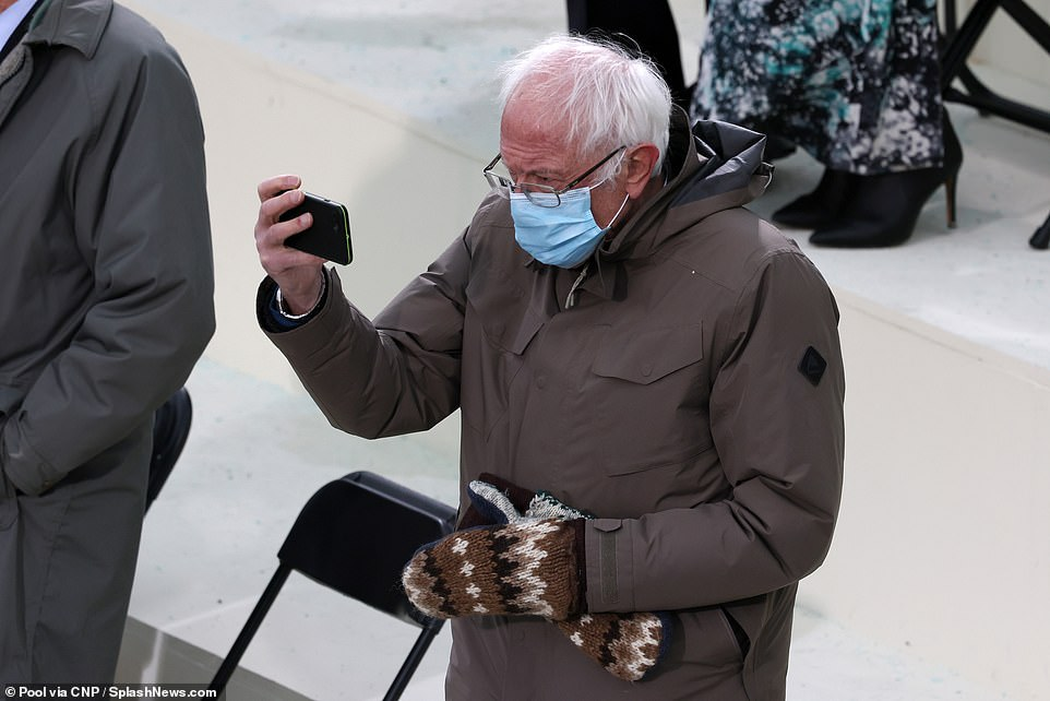 Bernie Sanders documents President Joe Biden's inauguration on his cellphone on Wednesday