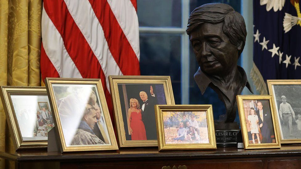 César Chávez's bus stands among family photos of Biden in the Oval Office.