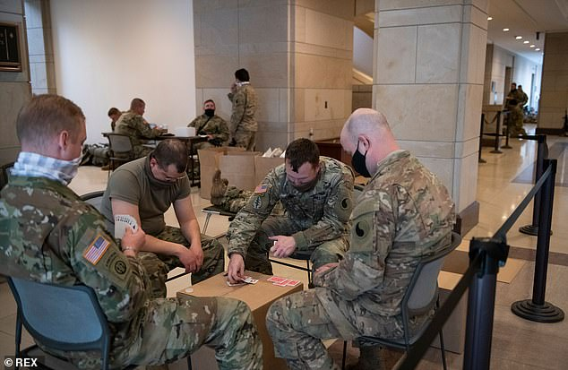 Members of the National Guard play cards in the Capitol Visitors Center at the US Capitol, the day after the inauguration of President Joe Biden in Washington, DC