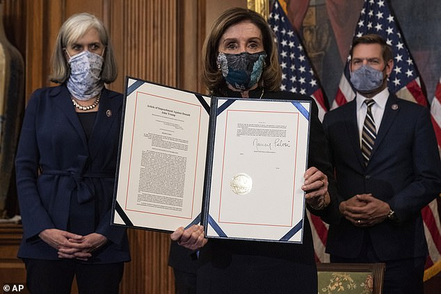House Speaker Nancy Pelosi of Calif., holds the article of impeachment against President Donald Trump after signing it, in an engrossment ceremony before transmission to the Senate for trial on Capitol Hill, in Washington, Wednesday, Jan. 13, 2021