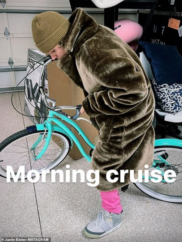 Riding out: He jumped on the back of a blue bicycle while wearing a heavy green fur coat for what he called: 'Morning cruise'
