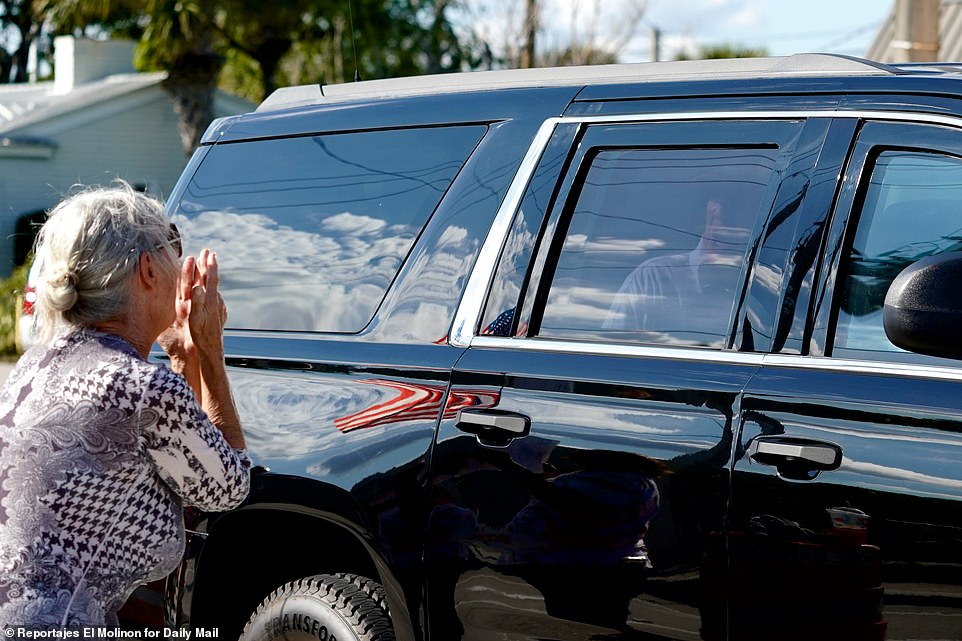 A woman shows her support for Trump as he drives by in his motorcade in Florida
