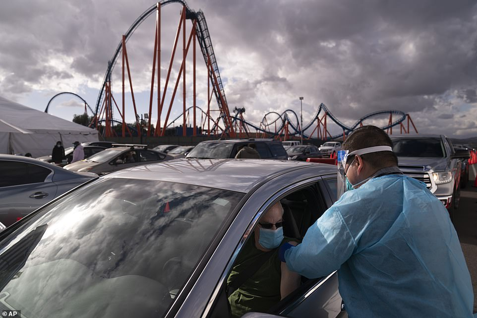 Licensed vocational nurse Joselito Florendo (right) administers the COVID-19 vaccine to Michael Chesler at a mass vaccination site set up in the parking lot of Six Flags Magic Mountain in Valencia, California, on Friday
