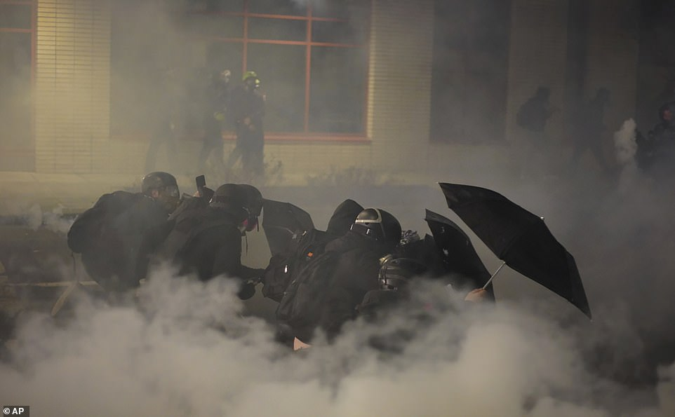 A group of protesters shield themselves from chemical irritants fired by police on Wednesday
