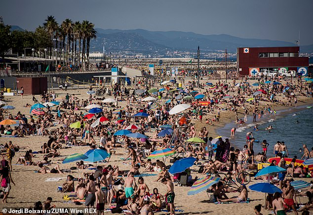 The plans will see all arrivals sent to airport hotels, regardless of their nationality and where they have come from. Pictured: Beach goers enjoy the sunshine at Nova Icaria beach in Barcelona amid the coronavirus pandemic