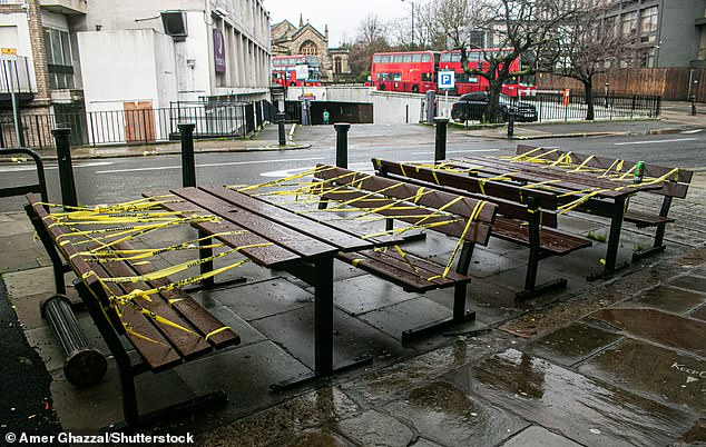 The move does not mean lockdown has been extended, but means the powers are in place should the Government decide to push back its current timetable. Pictured: A set of taped-off benches outside a pub in London