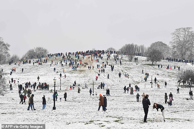 People play in the snow on Primrose Hill in Londonas the capital experiences a rare covering of snow on Sunday