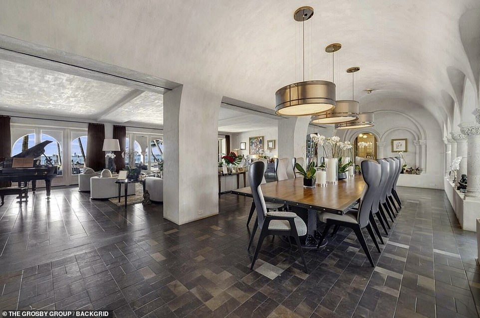 The mansion also features a wine cellar with an elevator and temperature control for 600-800 bottles. Pictured: A large dining area is pictured across from the lounge