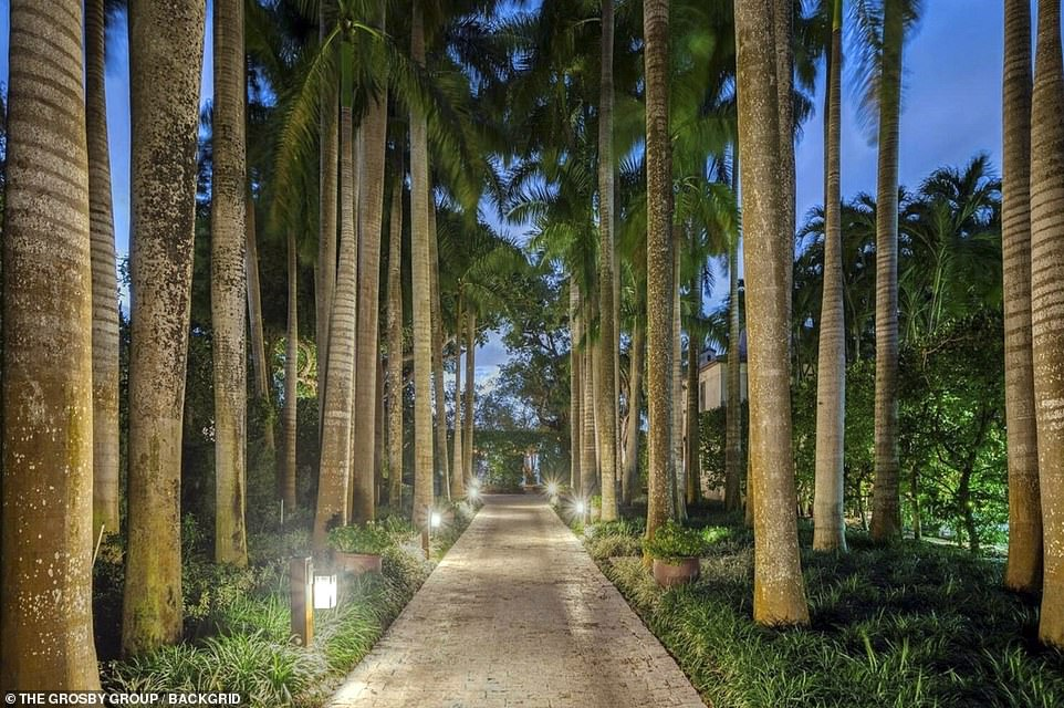 An ornate wrought-iron gate opens to a forest of curved coconut palm trees and a 6,000-gallon koi pond