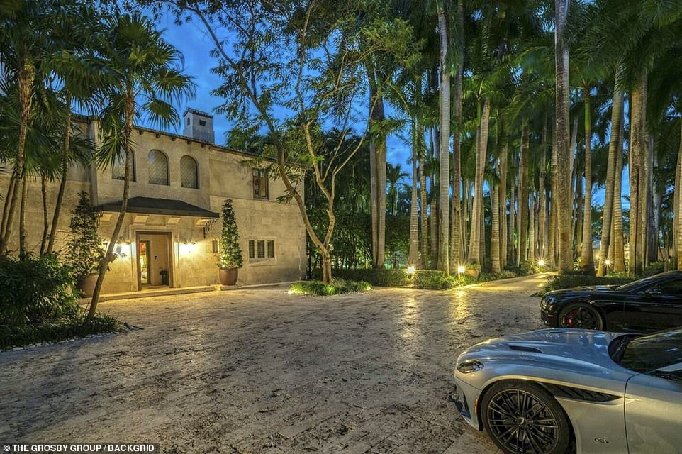 Parked cars in the outside area are surrounded by golden lanterns and scores of trees in the $40million Miami mansion