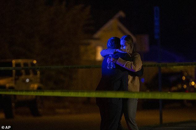 A man and a woman embrace as Austin police officers and members of SWAT work the scene late Tuesday