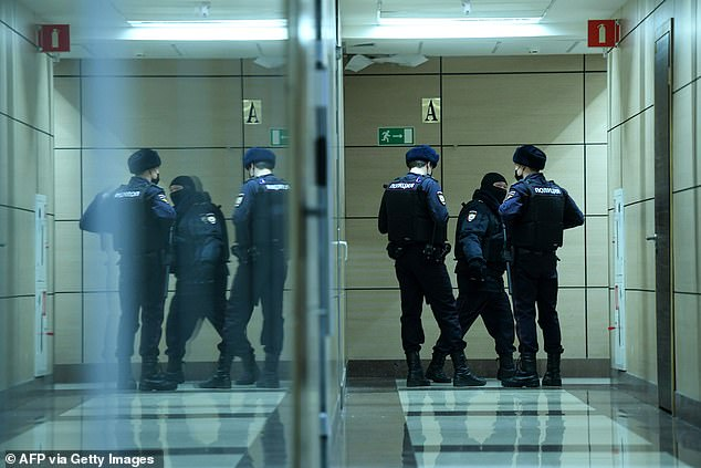 Police officers are seen preparing to search the offices of opposition leader Alexei Navalny's Anti-Corruption Foundation (FBK), in Moscow today