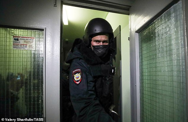 A police officer is seen outside the Moscow apartment of jailed Kremlin critic Alexei Navalny today